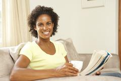 Stock Photo of woman reading book with drink at home
