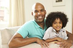 father and son relaxing on sofa at home - stock photo