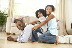 grandfather playing with grandchildren at home - stock photo