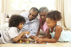 grandparents playing board game at home with grandchildren - stock photo