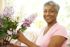 Stock Photo of senior woman flower arranging at home