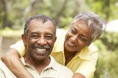 senior couple outdoors hugging - stock photo