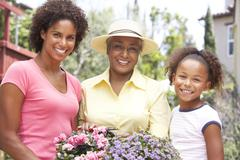 Senior woman with adult daughter and granddaughter gardening together Stock Photos