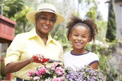 Grandmother with granddaughter gardening together Stock Photos