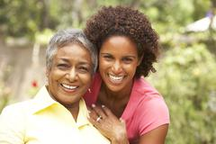 senior woman hugging adult daughter - stock photo