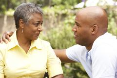 senior woman being consoled by adult son - stock photo
