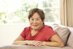 senior woman relaxing in chair at home - stock photo