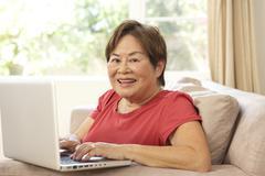 senior woman using laptop at home - stock photo