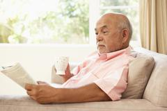 Senior man reading book with drink at home Stock Photos