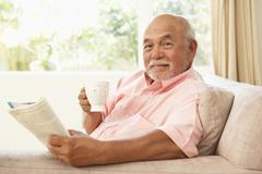 Stock Photo of senior man reading book with drink at home