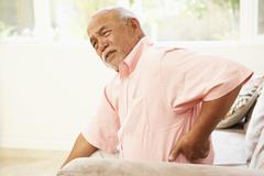 Senior man suffering from back pain at home Stock Photos