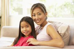 Mother and daughter relaxing on sofa at home Stock Photos
