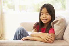 Young girl relaxing on sofa at home Stock Photos