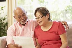 senior couple discussing document at home - stock photo