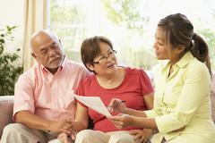 Senior couple talking to financial advisor at home Stock Photos