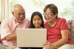 Grandparents and grandaughter using laptop computer at home Stock Photos
