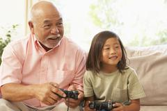 grandfather and grandson playing computer game at home - stock photo