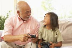 Grandfather and grandson playing computer game at home Stock Photos