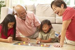 Grandparents and grandchildren playing board game at home Stock Photos