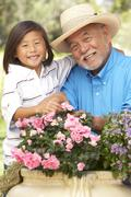 grandfather and grandson gardening together - stock photo