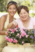 Mother with adult daughter gardening together Stock Photos