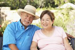 senior couple relaxing in garden together - stock photo