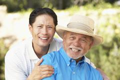 senior man with adult son in garden - stock photo