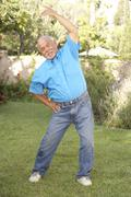Senior man exercising in garden Stock Photos