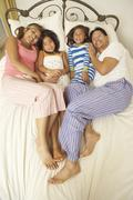 young family relaxing in bedroom - stock photo