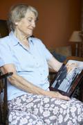 Senior woman at home looking at old wedding photo Stock Photos