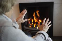 Senior woman warming hands by fire at home Stock Photos