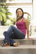 young woman sitting on steps of building - stock photo