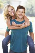 young man giving woman piggyback outdoors - stock photo