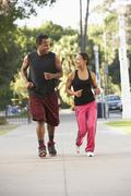 young couple jogging on street - stock photo