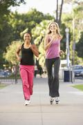 two female friends jogging on street - stock photo