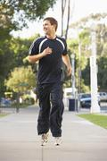 Young man jogging on street Stock Photos