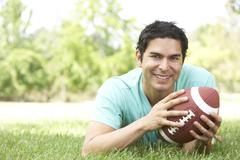 portrait of young man in park with american football - stock photo
