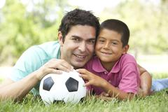 father and son in park with football - stock photo
