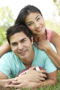 couple in park with american football - stock photo
