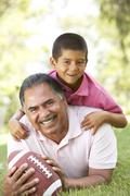 grandfather with grandson in park with american football - stock photo