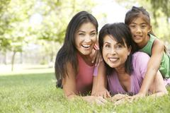 Grandmother with daughter and granddaughter in park Stock Photos
