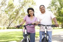 Senior couple riding bikes in park Stock Photos