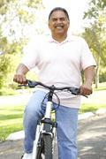 senior man riding bike in park - stock photo
