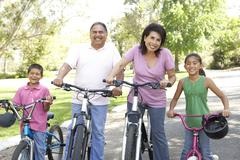 Grandparents in park with grandchildren riding bikes Stock Photos