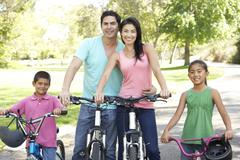 young family riding bikes in park - stock photo