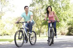 Young couple riding bike in park Stock Photos