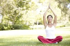 Young woman doing yoga in park Stock Photos