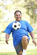 senior man exercising with football in park - stock photo