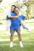Senior couple in sports clothing having fun in park Stock Photos