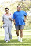 Senior couple jogging in park Stock Photos